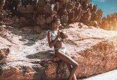 Νερό κοκοφοινίκων κατανάλωσης κοριτσιών Afro από τον κοντινό βράχο στοκ φωτογραφίες