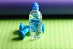 Νερό κοντά στο πλαστικό barbells στο χαλί γιόγκας αθλητισμός και υγεία στοκ εικόνα με δικαίωμα ελεύθερης χρήσης