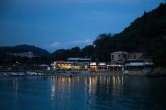 Νερό που απεικονίζει τα φω'τα από τα εστιατόρια Τα εστιατόρια λειτουργούν στο χρόνο σούρουπου Βάρκες πενταλιών, Recliners στην αν στοκ εικόνες με δικαίωμα ελεύθερης χρήσης