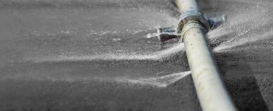 Νερό που διαρρέει από την τρύπα σε μια βιομηχανική μάνικα στοκ εικόνες με δικαίωμα ελεύθερης χρήσης