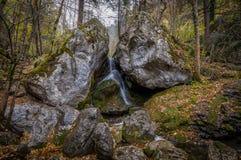 Νερό που πέφτει μεταξύ δύο μεγάλων βράχων στο δάσος φθινοπώρου σε Myrafälle στοκ εικόνα