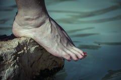 Νερό που στάζει από τα καυκάσια γυμνά πόδια γυναικών σε μια άκρη βράχου Στοκ Εικόνες