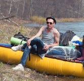 Νερό που ταξιδεύει - νεαρός άνδρας στο καπέλο και γυαλιά ηλίου στο καταμαράν τουριστών στο δασικό ποταμό Στοκ Εικόνες