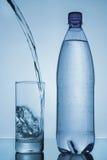 Νερό που χύνεται στο γυαλί και το μπουκάλι στο μπλε υπόβαθρο Στοκ Εικόνες