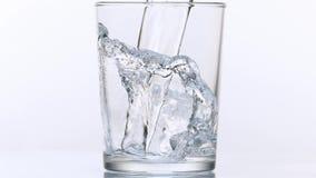 Νερό που χύνεται στο γυαλί στο άσπρο κλίμα φιλμ μικρού μήκους