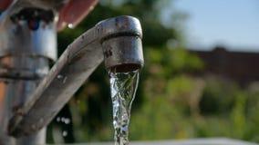 Νερό που ψεκάζει σε ετοιμότητα θηλυκά από μια μεταλλική στρόφιγγα το κ φιλμ μικρού μήκους