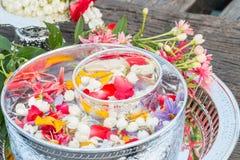 Νερό στο κύπελλο που αναμιγνύεται με το άρωμα και τα λουλούδια Στοκ Εικόνες