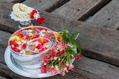 Νερό στο κύπελλο που αναμιγνύεται με το άρωμα και τα λουλούδια στοκ φωτογραφία