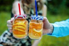 Νερό Detox με το πορτοκάλι και το λεμόνι Οι άνθρωποι πίνουν τη λεμονάδα Ο ομο Στοκ φωτογραφίες με δικαίωμα ελεύθερης χρήσης