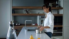 Νερό poors γυναικών στο τηγάνι απόθεμα βίντεο