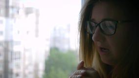 Νευρικές γυναίκες eyeglasses με τη διανοητηκή διαταραχή κοντά στο παράθυρο στο σπίτι απόθεμα βίντεο