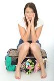 Νευρική ανήσυχη φοβησμένη νέα συνεδρίαση γυναικών σε μια ξεχειλίζοντας βαλίτσα στοκ εικόνες