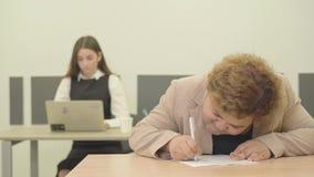 Νευρική νέα παχουλή γυναίκα που γράφει κάτω τη συνεδρίαση πληροφοριών στο σύγχρονο γραφείο στο πρώτο πλάνο ενώ λεπτός όμορφος της φιλμ μικρού μήκους