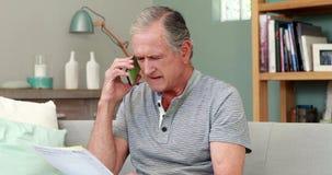 Νευρικό ανώτερο άτομο στο τηλέφωνο απόθεμα βίντεο