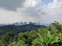 Νεφελώδης άποψη πόλεων με τον ορίζοντα πίσω από τη ζούγκλα στοκ εικόνες