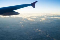 Νεφελώδης ουρανός κάτω από το φτερό ενός επιβατηγού αεροσκάφους Στοκ Εικόνα