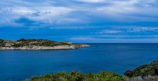 Νεφελώδης ουρανός πέρα από έναν μεγάλους βράχο και μια θάλασσα Στοκ Εικόνες