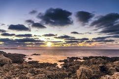 Νεφελώδεις ουρανοί σε αντίθεση με την άποψη θάλασσας βραδιού στοκ φωτογραφίες