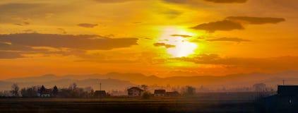 Νεφελώδες ηλιοβασίλεμα πέρα από το χωριό στοκ φωτογραφίες με δικαίωμα ελεύθερης χρήσης