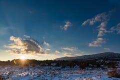 Νεφελώδες ηλιοβασίλεμα στον τομέα χιονιού με το βουνό Στοκ εικόνες με δικαίωμα ελεύθερης χρήσης