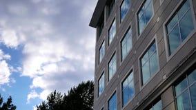 Νεφελώδης ουρανός με τη φωτισμένη απεικονισμένη πρόσοψη γυαλιού στο σύγχρονο κτίριο γραφείων φιλμ μικρού μήκους