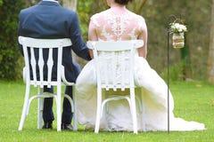 Νεόνυμφοι που κάθονται στις άσπρες καρέκλες woodem σε έναν κήπο στο βοτάνισμα της τελετής στοκ εικόνα