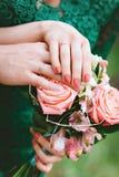 Νεόνυμφος και νύφη από κοινού Χέρια των newlyweds με τα δαχτυλίδια στην ανθοδέσμη Στοκ φωτογραφία με δικαίωμα ελεύθερης χρήσης