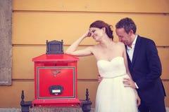 Νεόνυμφος και νύφη κοντά σε ένα ταχυδρομείο Στοκ φωτογραφία με δικαίωμα ελεύθερης χρήσης