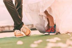 Νεόνυμφος και νύφη στα ζωηρόχρωμα plimsolls στον τάπητα Στοκ εικόνες με δικαίωμα ελεύθερης χρήσης