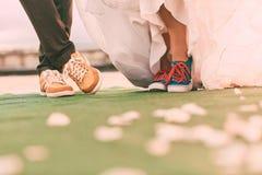 Νεόνυμφος και νύφη στα plimsolls στον πράσινο τάπητα με τα πέταλα Στοκ εικόνα με δικαίωμα ελεύθερης χρήσης