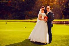 Νεόνυμφος και νύφη στον τομέα γκολφ Στοκ φωτογραφία με δικαίωμα ελεύθερης χρήσης