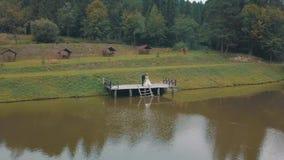 Νεόνυμφος με τη νύφη κοντά στη λίμνη στο πάρκο Γαμήλιο ζεύγος Εναέριος πυροβολισμός φιλμ μικρού μήκους