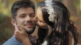 Νεόνυμφος με τη νύφη κοντά στους λόφους βουνών στο δασικό ζεύγος Παραγωγή ενός φιλιού απόθεμα βίντεο