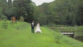 Νεόνυμφος με τη νύφη που περπατά κοντά στη λίμνη στο πάρκο Γαμήλιο ζεύγος o απόθεμα βίντεο