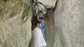 Νεόνυμφος με τη νύφη που στέκεται στη σπηλιά των λόφων βουνών Γαμήλιο ζεύγος ερωτευμένο φιλμ μικρού μήκους