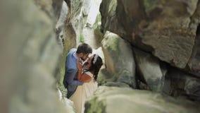 Νεόνυμφος με τη νύφη που στέκεται στη σπηλιά των λόφων βουνών Γαμήλιο ζεύγος ερωτευμένο απόθεμα βίντεο