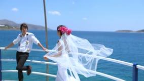 Νεόνυμφος νυφών στην παραλία μετά από το γάμο τους με το πέπλο νυφών ` s που φυσά με τον αέρα απόθεμα βίντεο