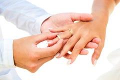 Νεόνυμφος που δίνει ένα δαχτυλίδι αρραβώνων στη νύφη του κάτω από το deco αψίδων Στοκ εικόνες με δικαίωμα ελεύθερης χρήσης