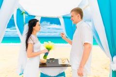 Νεόνυμφος που δίνει ένα δαχτυλίδι αρραβώνων στη νύφη του κάτω από το deco αψίδων Στοκ Εικόνες
