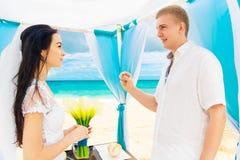 Νεόνυμφος που δίνει ένα δαχτυλίδι αρραβώνων στη νύφη του κάτω από το deco αψίδων Στοκ φωτογραφία με δικαίωμα ελεύθερης χρήσης