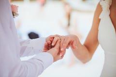 Νεόνυμφος που δίνει ένα δαχτυλίδι αρραβώνων στη νύφη του κάτω από το deco αψίδων Στοκ εικόνα με δικαίωμα ελεύθερης χρήσης