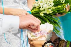 Νεόνυμφος που δίνει ένα δαχτυλίδι αρραβώνων στη νύφη του κάτω από το deco αψίδων Στοκ Φωτογραφία