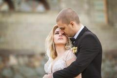 Νεόνυμφος που αγκαλιάζει τη νύφη στο υπόβαθρο του παλαιού κτηρίου στοκ φωτογραφίες