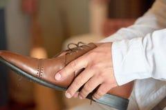 Νεόνυμφος που βάζει στα παπούτσια φορεμάτων Στοκ Εικόνα