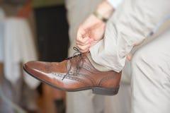 Νεόνυμφος που βάζει στα παπούτσια φορεμάτων Στοκ Φωτογραφία