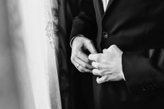 Νεόνυμφος που βάζει στο μοντέρνο μαύρο κοστούμι, το άσπρους πουκάμισο και το δεσμό τόξων Στοκ Φωτογραφίες