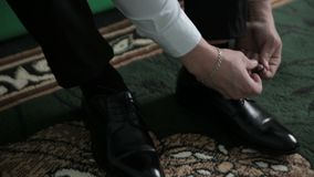 Νεόνυμφος που βάζει τα γαμήλια παπούτσια του Χέρια του γαμήλιου νεόνυμφου που παίρνουν έτοιμα στο κοστούμι απόθεμα βίντεο