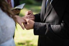 Νεόνυμφος που βάζει το δαχτυλίδι αρραβώνων στο δάχτυλο γυναικών Στοκ Εικόνες