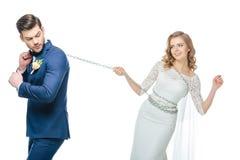Νεόνυμφος που κρατά τη νέα νύφη στην αλυσίδα απομονωμένη στο λευκό Στοκ Φωτογραφία