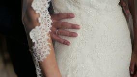 Νεόνυμφος που κρατά tenderly την εύθραυστη μέση της νύφης κοντά επάνω φιλμ μικρού μήκους